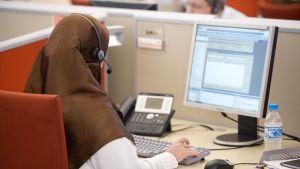 Muslimi nainen työskentelee puhelinkeskuksessa.