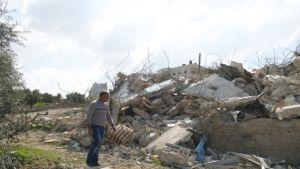 Khaled kävelee raunioituneen talonsa edessä.