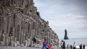 Turisteja basalttikiviesiintymällä eteläisessä Islannissa.