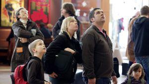 Matkustajat katsovat näyttötauluilta lentoaikataulujen muutoksia Brysselin kansainvälisellä lentoasemalla.