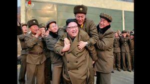 Pohjois-Korean välittämissä propagandakuvissa maan johtaja Kim Jong-un juhlii rakettimoottorikoetta. Kuvassa Kim reppuselässä on pohjoiskorealainen sotilas. Hänen ympärillään on suosiotaan osoittavia sotilaita.