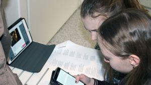 Oppillaat selaavat kännykkää.