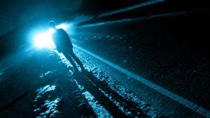 mies öisellä tiellä auton lähestyessä