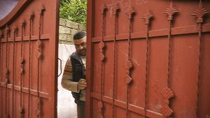 Mies avaa talonsa porttia.