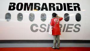 Nainen katsoo sisään Bombardie-yhtiön lentokoneen ikkunasta.