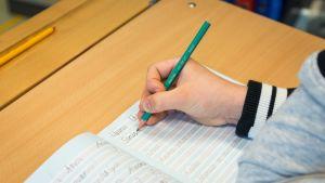 Koululainen tekee käsialatehtävää.
