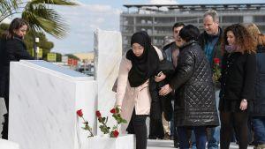 Ihmiset vievät kukkia Barcelonan lentokentällä olevalle muistopaikalle kukkia.