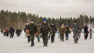 Kymmeniä pilkkijöitä kävelee järven jäällä.