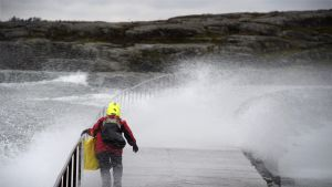 Nainen ylittää Uunisaaren aallonmurtajaa kovassa tuulessä meriveden lyödessä aallonmurtajan yli.