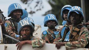 YK-sotilaita siniset kypärät päässä auton lavalla.