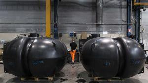 kaksi valmista jätevesisäiliötä Wavin-Labkon tehtaalla, työntekijä taustalla.