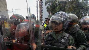 Kypäräpäisiä sotilaita läpinäkyvien kilpien takana.