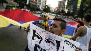 Etualalla mielenosoittaja pitää lappua kädessään. Taustalla mielenosoittajat pitelevät suurta Venezuelan lippua.