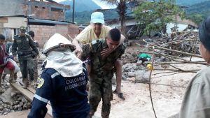 Sotilas kantaa lippalakkipäistä vanhaa naista selässään lankkusillalla, joka ylittää virtaavan veden. Taustalla näkyy mutavyöryn tuhoamaa kaupunkia. Sillan vieressä seisoo kypäräpäinen mies haalareissa. Toisella puolella näkyy sotilaita ja asukkaita.