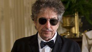 Dylan mustat aurinkolasit päässään, rusetti kaulassaan, tummassa puvussa.