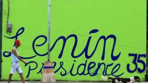 """Mies punaisessa lippalakissa, shortseissa ja hihattomassa paidassa kävelee vihreäksi maalatun seinän ohi. Seinään on maalattu sinisellä värillä ja isoin kirjaimin: Lenín presidente 35."""" Etualalla kulkee koira, jolla on mustavalkoinen turkki."""