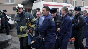 Poliisit ja pelastustyöntekijät kantoivat iskussa haavoittunutta hoitoon Pietarissa 3. huhtikuuta 2017.