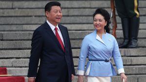 Xi ja Peng kävelevät punaista mattoa pitkin alas portaita.