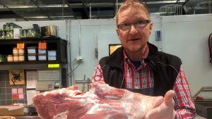 Lihakauppias Seppo Halonen esittelee kokonaista lammaspaistia.