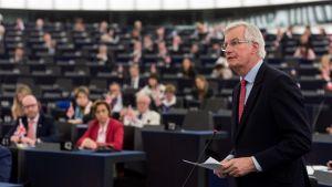 Michel Barnier seisoo pitämässä puhetta. Taustalla näkyy parlamentin istuntosalia ja euroedustajia.