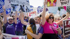 Joukko juhlivia ja halailevia naisia, naisilla on käsissään mielenosoitusjulisteita.