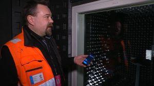 Oranssiliivinen mies soittaa kännykällä tummanpuhuvassa tilassa