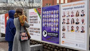 Ihmisiä katsomassa vaalijulisteita.