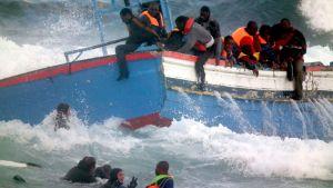 Vene on kallellaan myrskyävällä merellä. Osa ihmisistä on joutunut veden varaan.