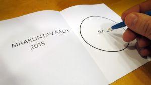 Miehen käsi kirjoittamassa numeroa äänestyslipukkeeseen