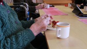 Toivolansaarikodin asukkaita pöydän ääressä syömässä piirakkaa