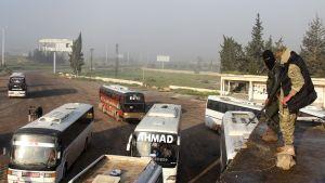 Ihmisiä evakuoidaan taistelujen alta. Joukko busseja on pysähdyksissä asvaltoidulla kentällä. Kaksi asemiestä naamiot kasvoillaan seisoo ajoneuvon katolla ja seuraa tilannetta.