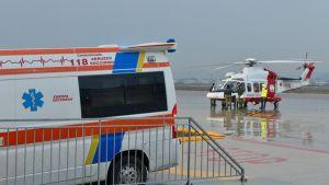 Helikopteri ja ambulanssi valmiina auttamaan Italian rannikkovartioston evakuoimia siirtolaisia tammikuussa 2017.