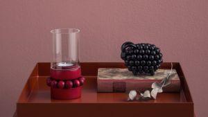 Aarikan esineitä pöydällä, kynttilänjalka ja pässi.