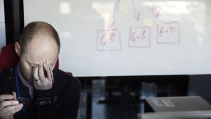 Työntekijä hieroo otsaansa työpöydän ääressä.