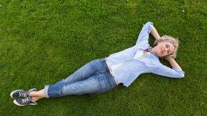 Nainen makaa nurmikolla