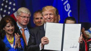 Yhdysvaltain presidentti Donald Trump esittelee allekirjoittamaansa viisumiasetusta.