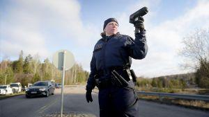 Poliisiviranomainen mittaa autojen nopeuksia nopeusvalvontaratsiassa.