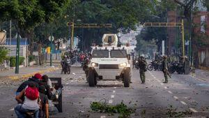 Mellakkapoliiisi valkoisen autonsa takana, mielensoittajat kyyristelevät pienen kilven takana kadulla Caracasissa