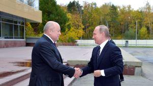 Venäjän presidentti Vladimir Putin kätteli ulkomaantiedustelun entisen johtajan Mihail Fradkovin kanssa vieraillessaan ulkomaantiedustelun päämajassa 5. lokakuuta 2016.