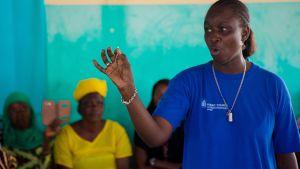 Nainen pitelee kädessään ehkäisykierukkaa, taustalla naisia yleisönä