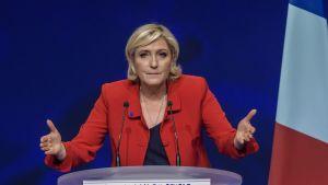 Marine Le Pen puhujakorokkeella punaisessa takissa