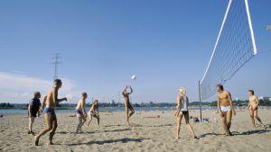 Auringonottajat pelaavat lentopalloa hiekkarannalla.
