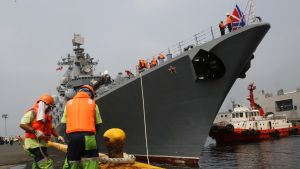 Suuri harmaa sotilasalus on Manilan satamassa. Kaksi filippiiniläistä satamatyöläistä oransseissa pelastusliiveissä ja oranssit kypärät päässään kiinnittää venäläisaluksen köyttä laituriin. Aluksen vieressä on hinaaja-alus.