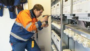 Jarkko Vehmas asentaa uusia älysähkömittareita kerrostalohuoneistoihin.