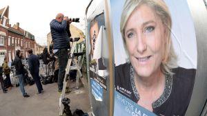 Marine Le Penin vaalimainos Henin-Beaumont'n äänestyspaikan edustalla Pohjois-Ranskassa 23. huhtikuuta.