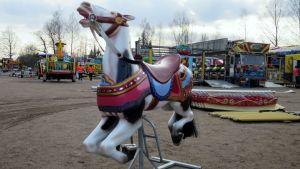 Karusellihevonen seisoo pakkamista odottamassahiekkakentällä
