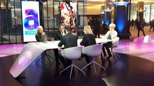 Keskustelijoita pöydän ääressä.