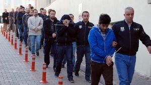 Pidätettyjä miehiä kuljetetaan käsikynkkää talon seinustan vierellä.