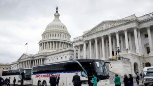 Senaattorit saapuvat busseilla Valkoiseen taloon.