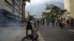 Mielenosoittajia kadulla. Yksi istuu maassa happinaamari päässään ja toinen pitelee häntä kiinni hartioista.